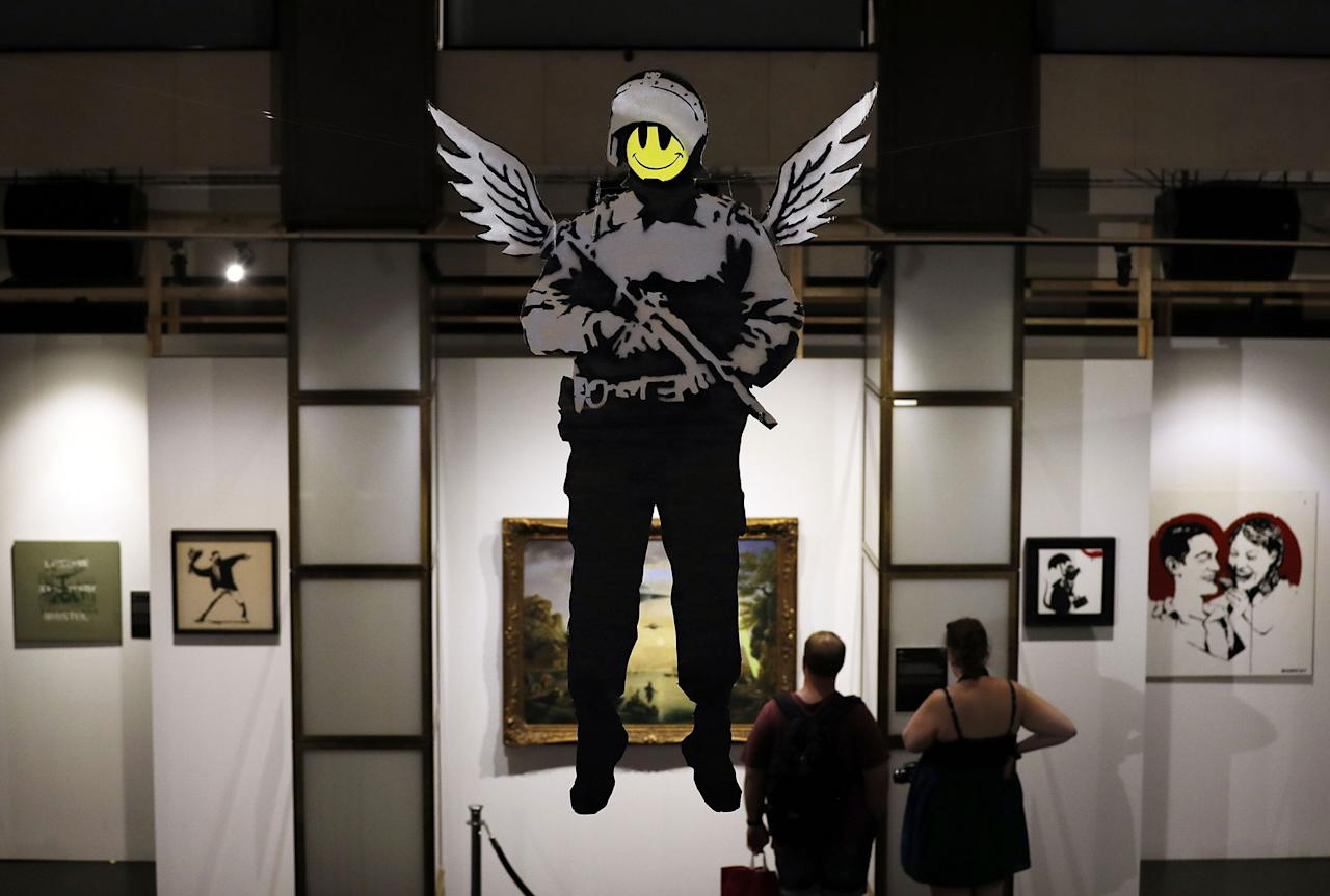 <p>A giant spray paint on card of the 'Flying Copper' by British Banksy is on display at the exhibition 'The Art of Banksy' in Berlin, Germany on June 20, 2017. (Felipe Trueba/EPA/REX/Shutterstock) </p>