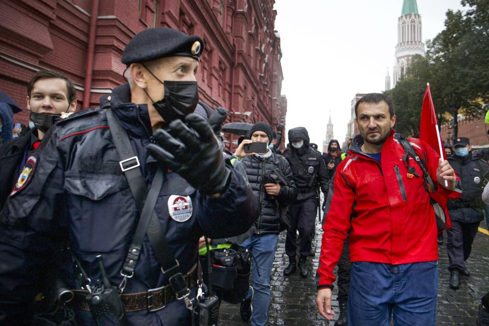 Police escort a demonstrator with a red flag during a protest against the results of the Parliamentary election near Red Square in Moscow, Russia, Saturday, Sept. 25, 2021. The Communist Party has called for a rally in Moscow on Saturday and was urged by the authorities Friday to remove the announcements from its website, otherwise it would be blocked — pressure that a party with seats in the parliament and which backs many of the Kremlin's policies has rarely faced before. (AP Photo/Vasily Krestyaninov)