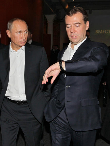 FILE - In this file photo taken Thursday, Dec. 1, 2011, Russian President Dmitry Medvedev, right, looks at his watch as he walks with Russian Prime Minister Vladimir Putin in Moscow. Medvedev is reported Thursday Feb. 7, 2013, that he intends to fix Russia permanently on Summer Time, with no immediate intention to change his previous decision. Medvedev ruled in 2011 that Russia would remain permanently fixed on Summer Time, but the rule has proved widely unpopular and President Putin has indicated that he may reverse the decision. (AP Photo/RIA-Novosti, Yekaterina Shtukina, Government Press Service)