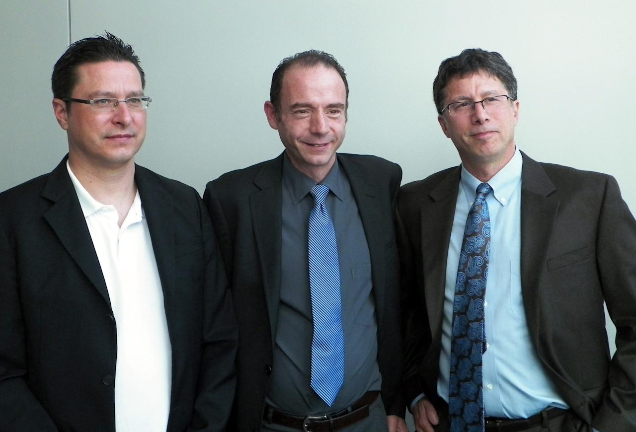 German Dr. Gero Hutter, left, Timothy Ray Brown, center, and Washington University Dr. David Curiel pose for a picture after Hutter discussed his treatment of Brown at a symposium on gene therapy cures at Washington University on Wednesday, Sept. 12, 2012, in St. Louis. Brown was diagnosed with HIV in 1995. In 2007 he had a blood gem cell transplant to treat leukemia using a donor with a rare gene mutation that provides natural resistance to HIV. Hutter says that resistance transferred to Brown and that enough time has passed to say without hesitation that he is cured of HIV. (AP Photo/Jim Salter)