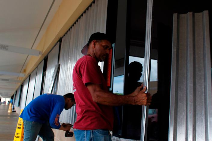 Workers install storm shutters as hurricane Irma approaches Puerto Rico in Fajardo.