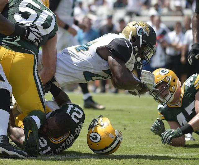<p>Jacksonville Jaguars running back T.J. Yeldon dives over the goal line past Green Bay Packers inside linebacker Blake Martinez (50) and free safety Ha Ha Clinton-Dix (21) for a touchdown during the first half of an NFL football game in Jacksonville, Fla., Sunday, Sept. 11, 2016. (AP Photo/Phelan M. Ebenhack) </p>