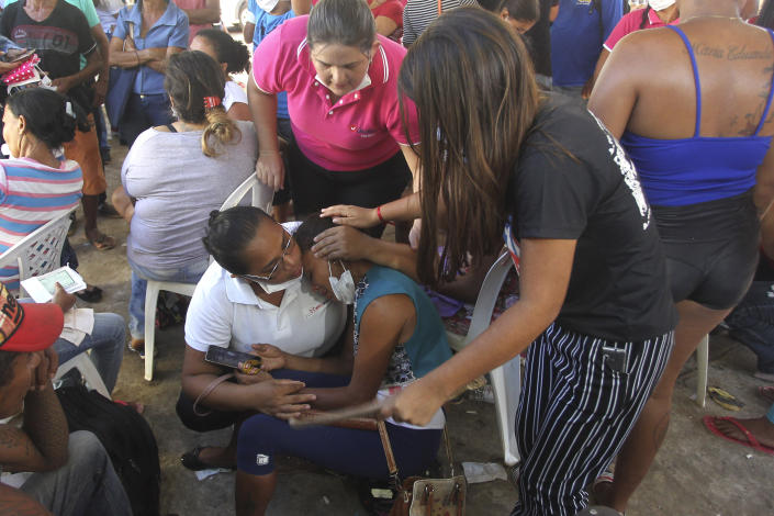 A woman comforts her daughter outside the coroner's office in Altamira, Brazil, Tuesday, July 30, 2019. Relatives of inmates killed during a prison riot in northern Brazil gathered at the coroner's office Tuesday to identify the 57 victims, with some passing out at seeing the beheaded corpse of a loved one. (AP Photo/Raimundo Pacco)