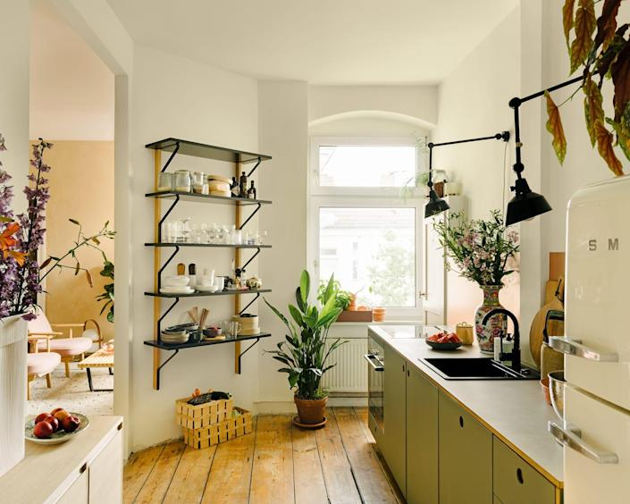 """Jules and Alhadj broke through the wall between the """"Berlin room"""" and the kitchen themselves. Midgard lights provide good work lighting, while Artek's Kaari shelf offers space for dishes and spices. The new cabinet fronts are from Reform. (We actually did a deeper dive into her kitchen last year.)"""