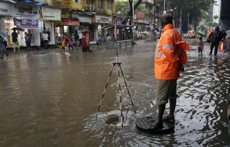 A Municipal officer stands guard to warn pedestrians of an open manhole on a waterlogged street following rainfall in Mumbai, India, Friday, June 28, 2019. India receives its monsoon rains from June to October. (AP Photo/Rajanish Kakade)