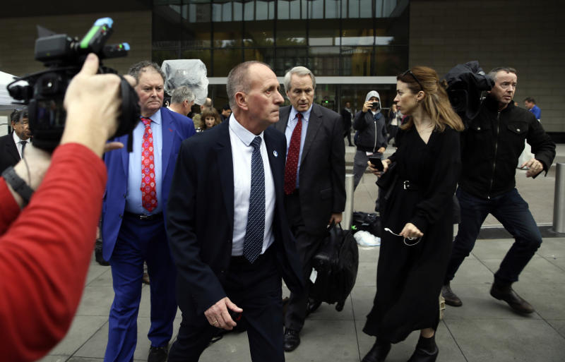 """British cave explorer Vernon Unsworth, center, with his attorneys, Mark Stephens, second from left, and L. Lin Wood, right, walk out of Los Angeles U.S. District Court Friday, Dec. 6, 2019. A Los Angeles jury has found Elon Musk did not defame the British cave explorer when he called him """"pedo guy"""" in an angry tweet. Unsworth, who participated in the rescue of 12 boys and their soccer coach trapped for weeks in a Thailand cave last year, had angered the Tesla CEO by belittling his effort to help with the rescue as a """"PR stunt."""" (AP Photo/Damian Dovarganes)"""
