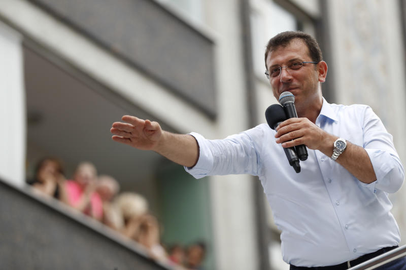 In this Wednesday, June 19, 2019 photo, Ekrem Imamoglu, candidate of the secular opposition Republican People's Party, or CHP, waves to supporters as he speaks at a rally in Istanbul, ahead of the June 23 re-run of Istanbul elections. Voters in Istanbul return to the polls on Sunday for a rerun of the election for the mayor of the city. (AP Photo/Lefteris Pitarakis)