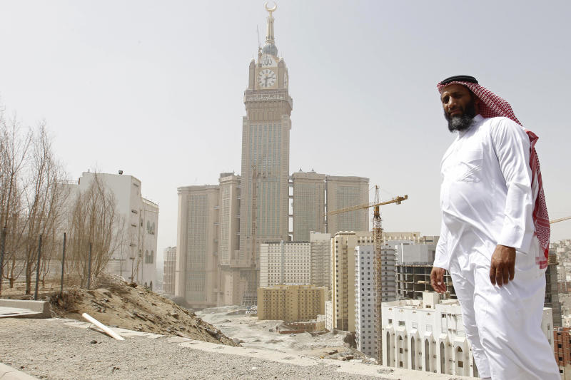 Ahmed Zuhair poses for a photo backdropped by the four-faced clock, atop the Abraj Al-Bait Towers, in the Saudi holy city of Mecca, Saudi Arabia, Friday, June 14, 2013. Until he was released from U.S. custody in 2009, Zuhair and another prisoner had the distinction of staging the longest hunger strikes at the Guantanamo prison. Zuhair kept at it for four years in a standoff that at times turned violent. Zuhair, a former sheep merchant who was never charged with any crime during seven years at Guantanamo, stopped eating in June 2005 and kept up his protest until he was sent home to Saudi Arabia in 2009. (AP Photo)