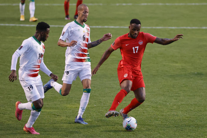 Canada's Cyle Larin (17) is defended by Suriname's Ryan Koolwijk (6) and Shaquille Pinas (19) during the first half of a World Cup 2022 Group B qualifying soccer match Tuesday, June 8, 2021, in Bridgeview, Ill. (AP Photo/Kamil Krzaczynski)