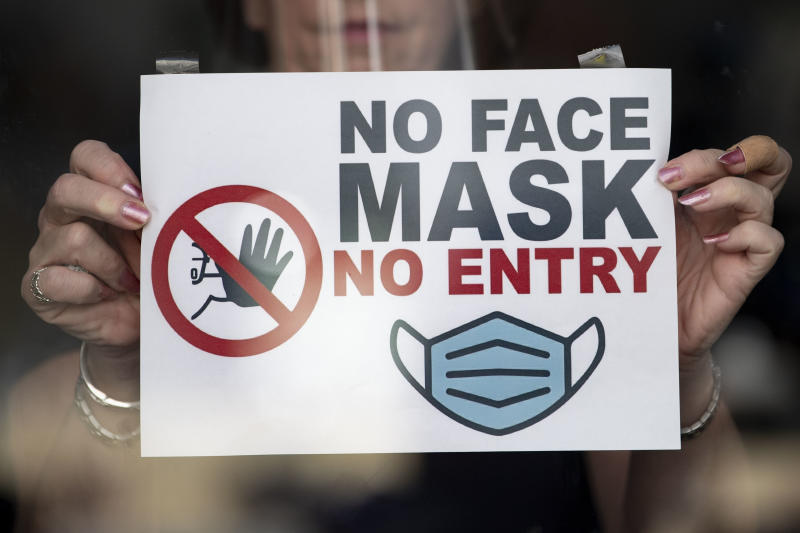 """NEWPORT, WALES - SEPTEMBER 14: In this photo illustration a woman puts a sign saying """"no face mask no entry"""" in a shop window on September 14, 2020 in Newport, Wales. First Minister of Wales Mark Drakeford has announced people in Wales must wear face mask in shops and other indoor public spaces from Monday. Indoor meetings of more than six from an extended household will be illegal from Monday. The rule will not apply to children under 11 and up to 30 people from different homes can still meet outside. (Photo by Matthew Horwood/Getty Images)"""