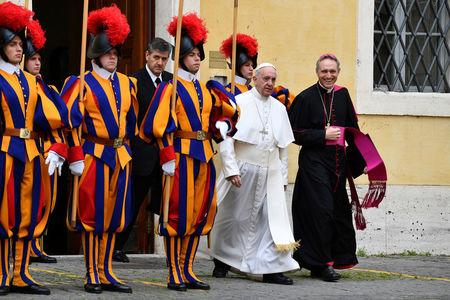 Pope Francis, flanked by Archbishop Georg Gaenswein, walks past Swiss Guards on is way to a private audience with Britain's Prince Charles and his wife Camilla, Duchess of Cornwall, at the Vatican, April 4, 2017.  REUTERS/ Vincenzo Pinto/Pool