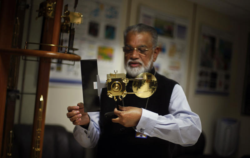 In this Thursday, Oct. 31, 2013 photo, Chairman of the Indian Space and Research Organization (ISRO) K. Radhakrishnan holds a model of Mars orbiter at his office in New Delhi, India. India is aiming to join the world's deep-space pioneers with a journey to Mars that it hopes will showcase its technological ability to travel our solar system while seeking solutions for everyday problems on Earth. (AP Photo/Altaf Qadri)