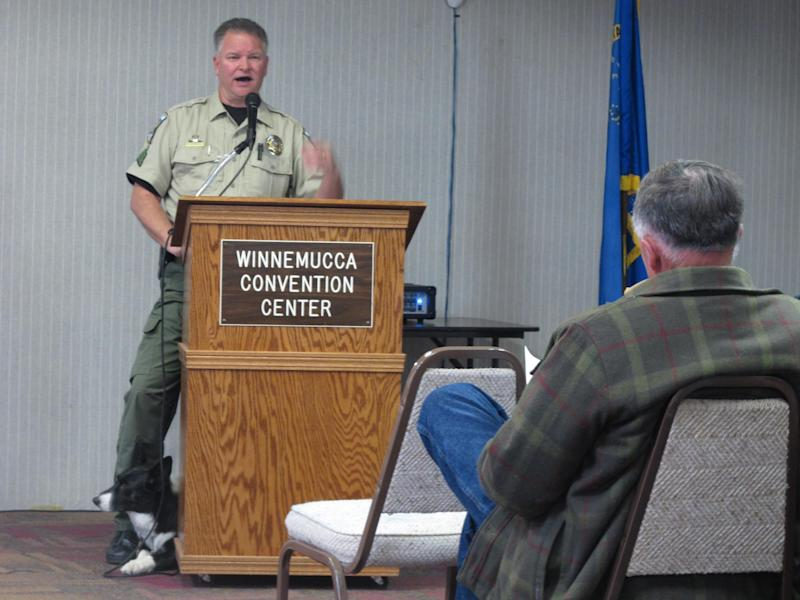 Humboldt County Sherriff's Sgt. Chris Aker describes the county's drug interdiction program on U.S. Interstate 80 in Winnemucca, Nev., Tuesday, March 11, 2014, as his K-9 ``Boots'' peers out from behind the podium during a public meeting at the Winnemucca Convention Center. About 40 people attended as Sheriff Ed Kilgore and others helped respond to questions about two federal lawsuits recently filed accusing county deputies of seizing tens of thousands of dollars without bringing criminal charges against suspected drug traffickers. (AP Photo/Scott Sonner)