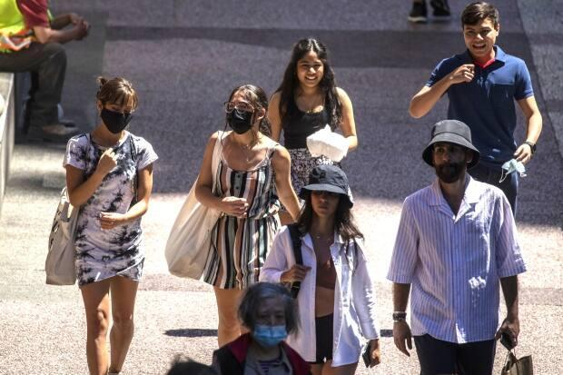 People are seen walking down a sidewalk with facemasks on in downtown Vancouver, British Columbia on Tuesday, June 22, 2021.  (Ben Nelms/CBC - image credit)