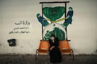 Tahani al-Rifi sits on a bench in front of a coronavirus-inspired mural in Gaza, from where she is unable to leave to receive treatment for cancer