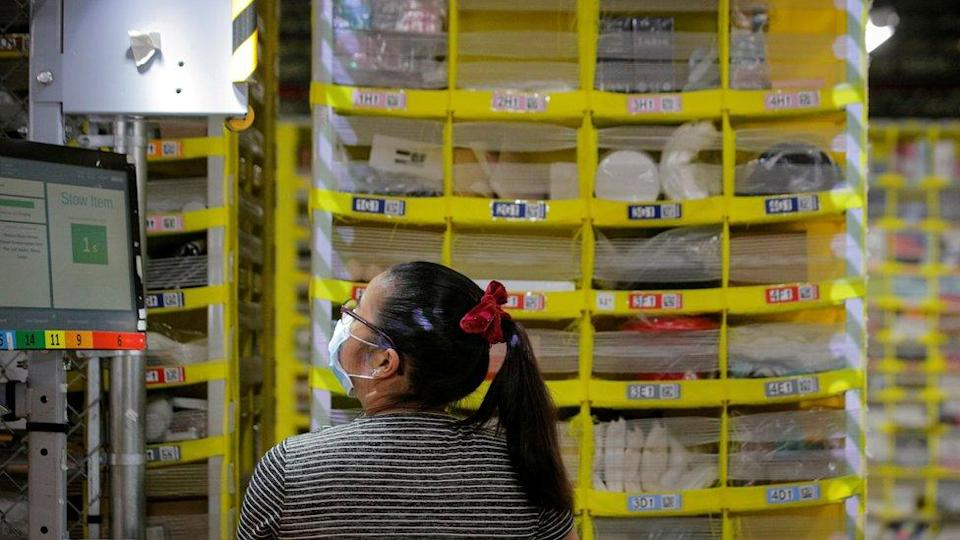 An employee fills a cart full of items at Amazon