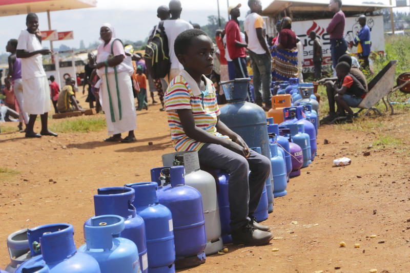 A young boy sits in a queue for cooking gas in Harare, Zimbabwe, Sunday, March, 29, 2020. Zimbabwean President Emmerson Mnangagwa announced a nationwide lockdown for 21 days, starting March 30, in an effort to stop the spread of the COVID-19 pandemic. The COVID-19 coronavirus causes less serious symptoms for most people, but for some, especially older adults and people with existing health problems, it can cause severe illness and even death. (AP Photo/Tsvangirayi Mukwazhi)