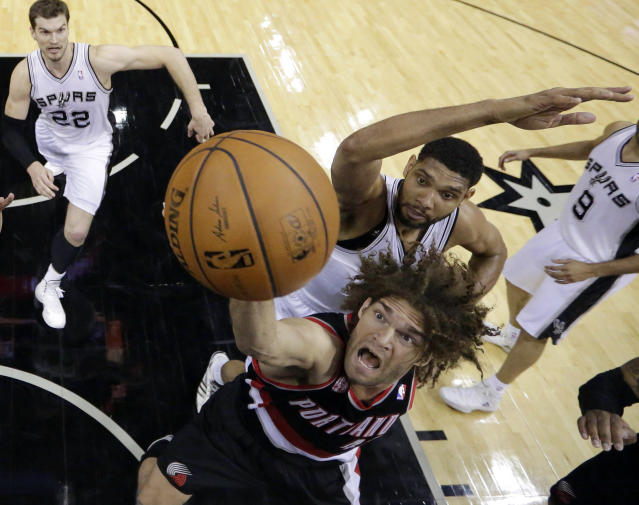 Portland Trail Blazers' Robin Lopez, front, shoots under San Antonio Spurs' Tim Duncan, back center, during the first half of Game 1 of a Western Conference semifinal NBA basketball playoff series, Tuesday, May 6, 2014, in San Antonio. (AP Photo/Eric Gay)