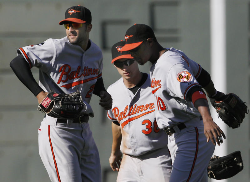Baltimore Orioles' Nick Markakis, left,  Matt Angle, center, and Adam Jones celebrate in the outfield at Fenway Park after they defeated the Boston Red Sox 6-5 in the first game of a day-night doubleheader baseball game in Boston, Monday, Sept. 19, 2011. (AP Photo/Elise Amendola)