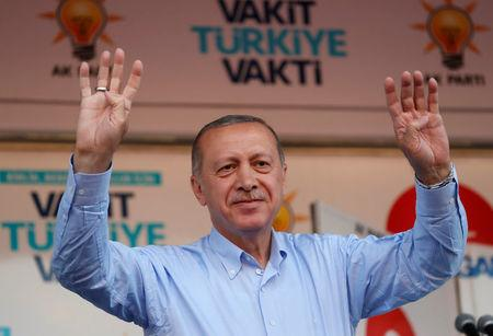 Turkish President Tayyip Erdogan holds up hands during  a rally in Mardin