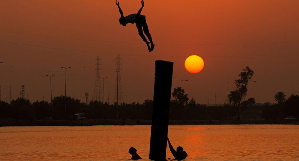 TOPSHOT - Iraqi youth swim in the Shatt Al-Arab river by the port of Maqil amid a heatwave in the southern Iraqi city of Basra on June 29, 2021. (Photo by Hussein FALEH / AFP) / The erroneous mention[s] appearing in the metadata of this photo by Hussein FALEH has been modified in AFP systems in the following manner: June 29, 2021] instead of [March 21, 2021]. Please immediately remove the erroneous mention[s] from all your online services and delete it (them) from your servers. If you have been authorized by AFP to distribute it (them) to third parties, please ensure that the same actions are carried out by them. Failure to promptly comply with these instructions will entail liability on your part for any continued or post notification usage. Therefore we thank you very much for all your attention and prompt action. We are sorry for the inconvenience this notification may cause and remain at your disposal for any further information you may require. (Photo by HUSSEIN FALEH/AFP via Getty Images)