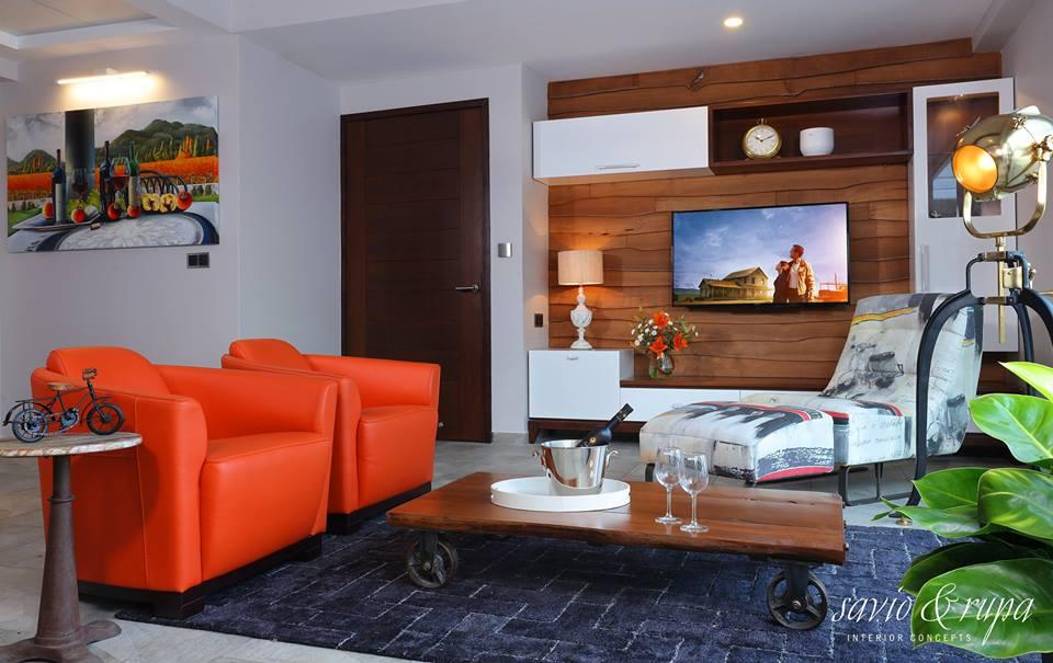 Lounge where the TV is mounted on a wall with raw edged teak wood planks as backdrop.