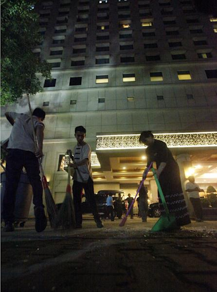 Staff clean up outside the Traders Hotel in Yangon, Myanmar Tuesday, Oct 15, 2013 following an explosion just before midnight Monday, which ripped apart a guest's 9th floor bathroom and slightly wounded an American woman in the latest in a series of unexplained blasts to hit the Southeast Asian country. It was not immediately clear what caused the explosion but the incident came after unidentified assailants planted three homemade bombs in and around Yangon in recent days, reportedly killing two people and injuring three others. (AP Photo/Khin Maung Win)