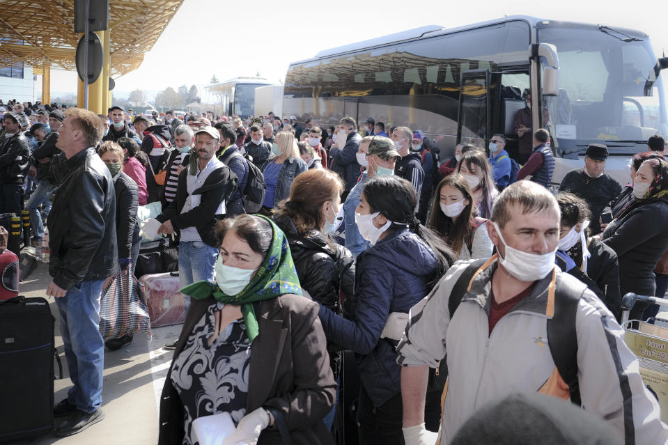 Romanian seasonal workers wait outside the Avram Iancu international airport, in Cluj, central Romania, Thursday, April 9, 2020. More then 1800 workers from across Romania are traveling on 12 flights to Berlin, Baden Bade and Dusseldorf in Germany, most of them to work in asparagus farms.(AP Photo/Raul Stef)