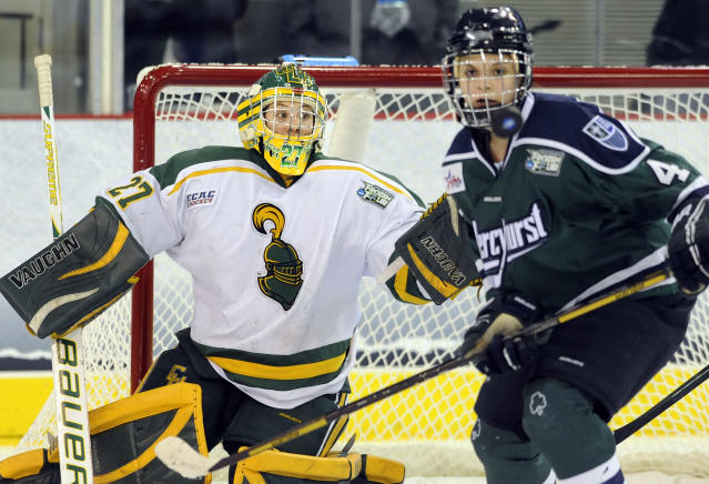 Clarkson's goaltender Erica Howe and Mercyhurst's Emily Janiga watch a loose puck during first period in an NCAA college hockey game in the semifinals of the women's Frozen Four in Hamden, Conn., Friday, March 21, 2014. (AP Photo/Fred Beckham)