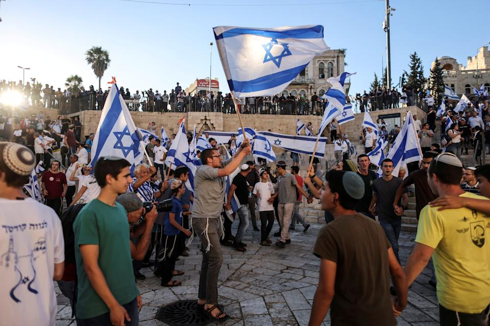 Israelis dance with flags by Damascus gate just outside Jerusalem's Old City June 15, 2021. REUTERS/Ronen Zvulun     TPX IMAGES OF THE DAY