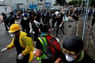 Riot police try to disperse protesters near a flag raising ceremony for the anniversary of Hong Kong handover to China in Hong Kong