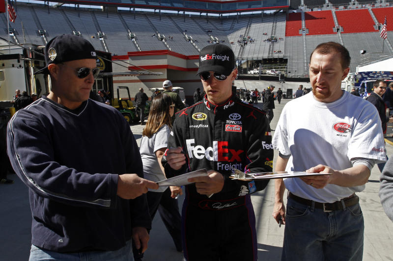 Driver Denny Hamlin, center, signs autographs before practice for the NASCAR Sprint Cup series auto race at Bristol Motor Speedway on Friday, March 14, 2014, in Bristol, Tenn. Hamlin will start from the pole position for Sunday's race. (AP Photo/Wade Payne)