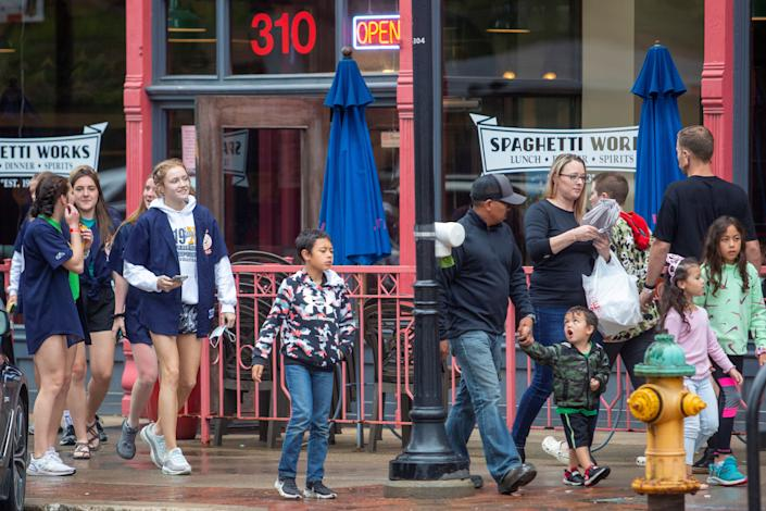 Groups of people walk in the Court Ave. district of Des Moines, Iowa, after Gov. Kim Reynolds signed a bill into law that bans future mask mandates for schools, cities and counties, May 20, 2021.  REUTERS/Rachel Mummey