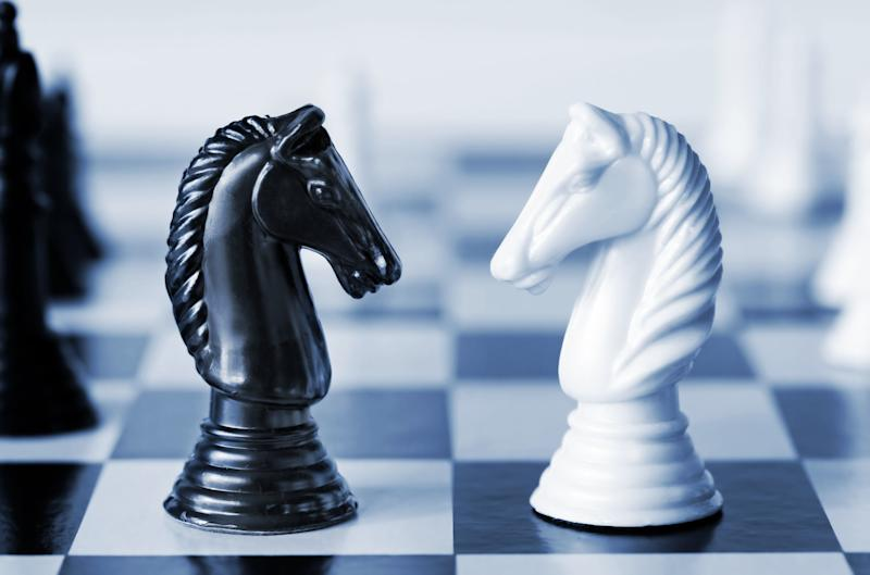 Head to head - knights on a chess board, in blue duotone. Shallow depth of field. (Photo: robynmac via Getty Images)