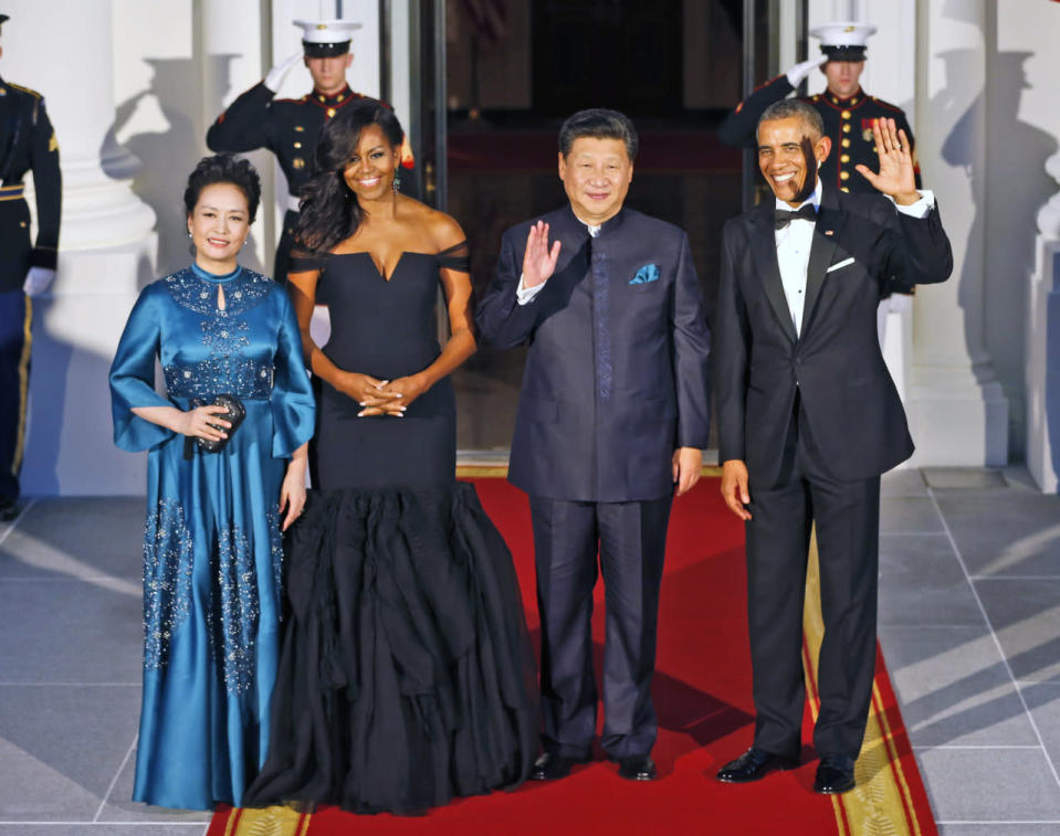 <p>While the first lady opted for the darker shade, Peng Liyuan, her Chinese equivalent shined in a satin aqua blue dress. The piece featured three-quarter trumpet sleeves, a keyhole neckline, and pearl and diamond embellishment placed throughout. Her husband, President Xi Jinping, wore a traditional Chinese navy blue blazer and trousers, with a pocket square matching the color of his wife's dress. </p>