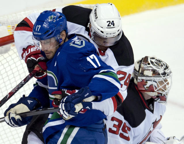 New Jersey Devils defenseman Bryce Salvador (24) tries to clear Vancouver Canucks center Ryan Kesler (17) from in front of New Jersey Devils goalie Cory Schneider (35) during the first period of an NHL hockey game Tuesday, Oct. 8, 2013, in Vancouver, British Columbia. (AP Photo/The Canadian Press, Jonathan Hayward)