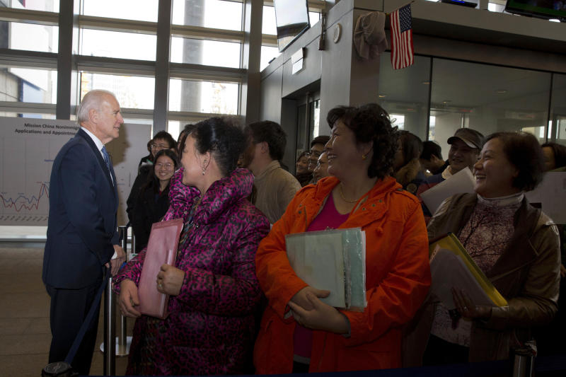 U.S. Vice President Joe Biden talks to visa applicants at the U.S. Embassy Consular Section in Beijing Wednesday, Dec. 4, 2013. (AP Photo/Ng Han Guan, Pool)