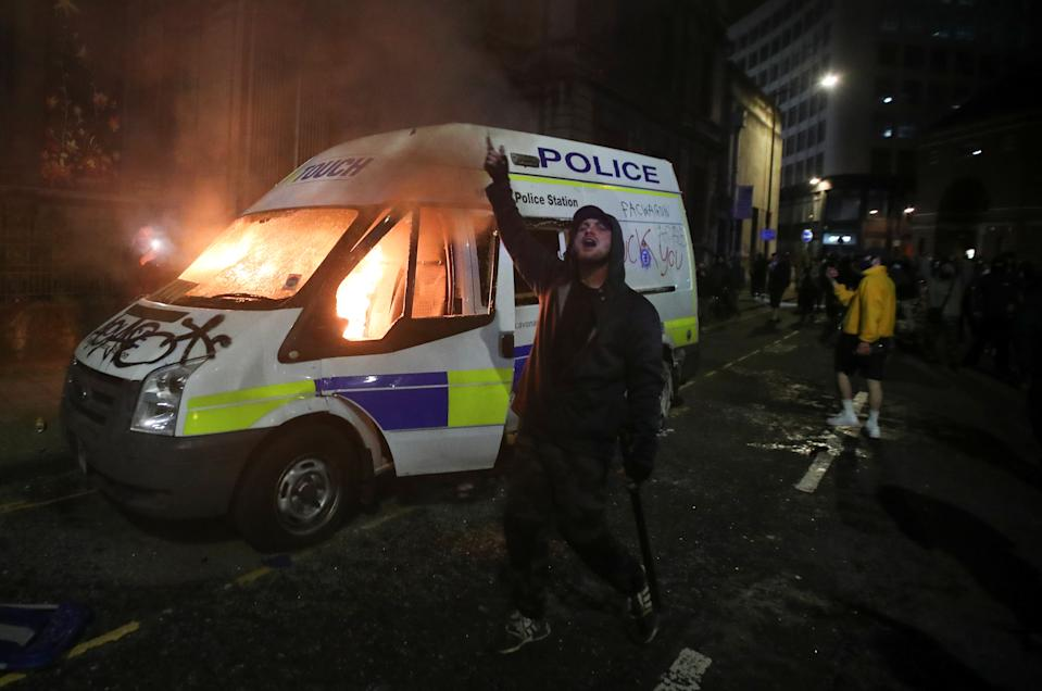<p>A demonstrator gestures in front of a burning police vehicle during a protest against a new proposed policing bill, in Bristol, Britain, March 21, 2021. REUTERS/Peter Cziborra</p>