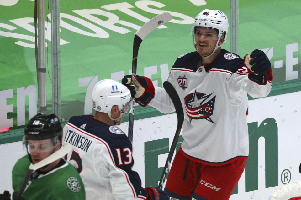 Columbus Blue Jackets right wing Cam Atkinson (13) celebrates a goal by center Jack Roslovic (96) against the Dallas Stars during the first period during an NHL hockey game on Thursday, April 15, 2021, in Dallas. (AP Photo/Richard W. Rodriguez)