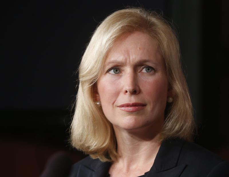 """FILE - In this photo taken July 16, 2013, Sen. Kirsten Gillibrand, D-N.Y., listens to a fellow senator speak to reporters about a bill regarding sexual assault in the military on Capitol Hill in Washington. Gillibrand has a deal with Ballantine to write a book, currently untitled, that will be a memoir and a """"call to action"""" for women. The publisher, an imprint of Random House Inc., announced Monday, Aug. 12, that the book was scheduled for Fall 2014. (AP Photo/Charles Dharapak, File)"""