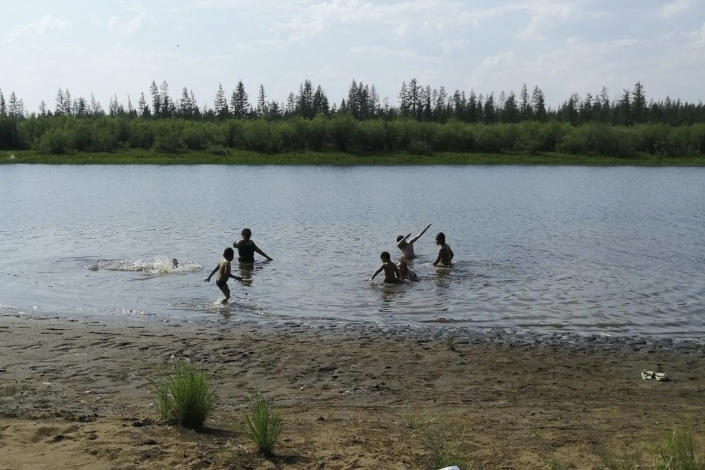 FILE - In this Sunday, June 21, 2020 photo provided by Olga Burtseva, children play in the Krugloe lake outside Verkhoyansk, Sakha Republic, about 4,660 kilometers (2,900 miles) northeast of Moscow, Russia. Russia's meteorological service said the thermometer hit 38 Celsius (100.4 F) the previous day in Verkhoyansk. A study by international scientists released Wednesday, July 15, 2020, says the 2020 freak Siberian heat wave is nearly impossible without man-made global warming (Olga Burtseva via AP)