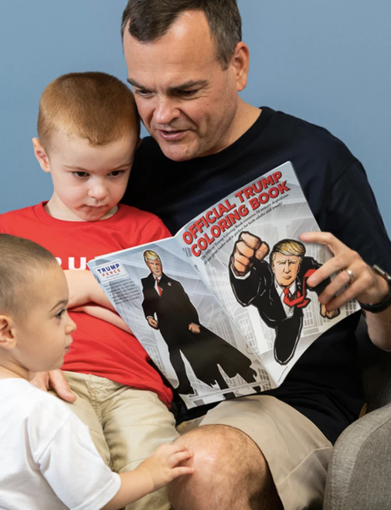 A man with two children reading the Donald Trump-endorsed colouring book