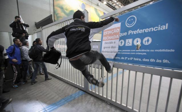 A commuter jumps and kicks an entrance gate in attempt to break it, at Itaquera subway station in Sao Paulo June 5, 2014. Union workers of Sao Paulo's Metro subway system are on strike since midnight, with just a week to go before the 2014 World Cup opens in Brazil, local media reported. REUTERS/Chico Ferreira (BRAZIL - Tags: SPORT SOCCER WORLD CUP CIVIL UNREST POLITICS TRANSPORT)