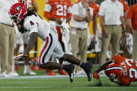Georgia running back James Cook (4) is tackled by Clemson cornerback Andrew Booth Jr., bottom right, during the first half of an NCAA college football game Saturday, Sept. 4, 2021, in Charlotte, N.C. (AP Photo/Chris Carlson)