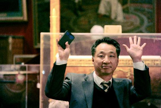 The South Korean buyer of one of Napoleon's famous two-pointed hats gestures at the Osenat auction house in Fontainebleau, on November 16, 2014 (AFP Photo/DOMINIQUE FAGET)
