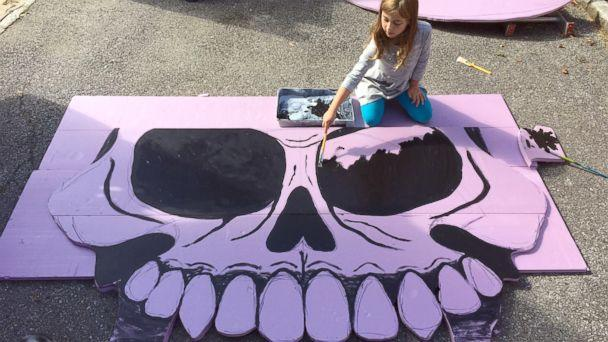 PHOTO: Michael Fry's eldest daughter Eily helping paint their giant skull decoration in 2016. (Michael Fry)