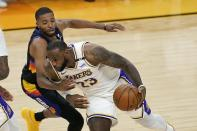 Los Angeles Lakers forward LeBron James (23) drives past Phoenix Suns forward Mikal Bridges, left, during the first half of Game 1 of an NBA basketball first-round playoff series Sunday, May 23, 2021, in Phoenix. (AP Photo/Ross D. Franklin)