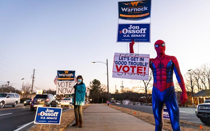 A person dressed in a Spider-Man costume holds campaign signs for Senate candidates near a polling location in Marietta, Georgia - Bloomberg