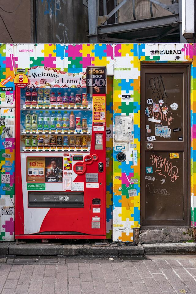 A vending machine is tucked into an alcove covered in a puzzle-piece print on a street in Ueno, Tokyo.