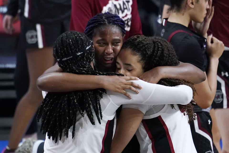 South Carolina forward Aliyah Boston, center, gets a hug from Stanford forward Francesca Belibi, left, and guard Haley Jones, right, after a women's Final Four NCAA college basketball tournament semifinal game Friday, April 2, 2021, at the Alamodome in San Antonio. Stanford won 65-66. (AP Photo/Eric Gay)